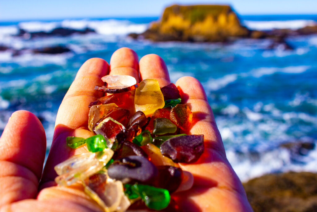 Man holds glass pebbles in Glass Beach, Fort Bragg, California.