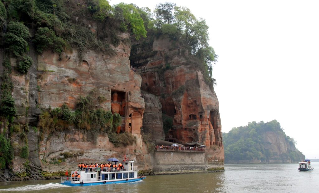 A boat going past the Leshan Giant Buddha.
