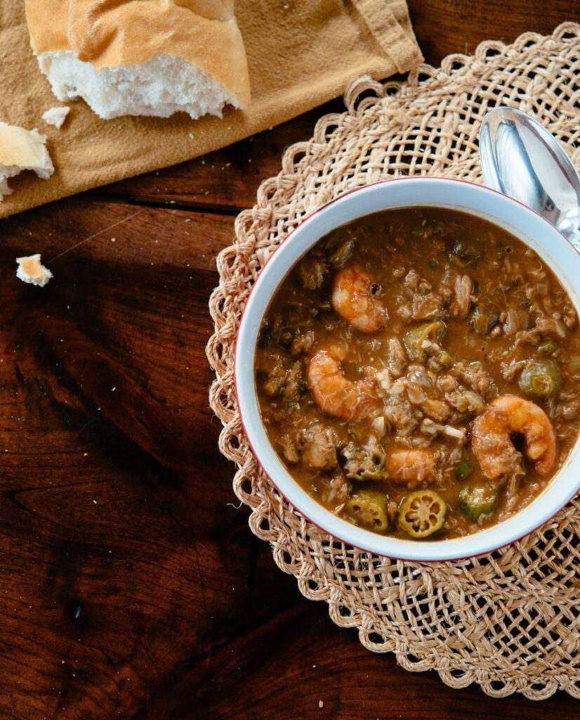 A bowl of gumbo with bread.