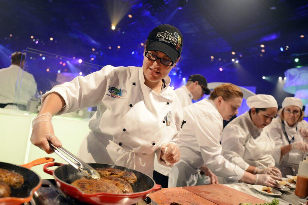 A chef prepares food at a Disney World event.