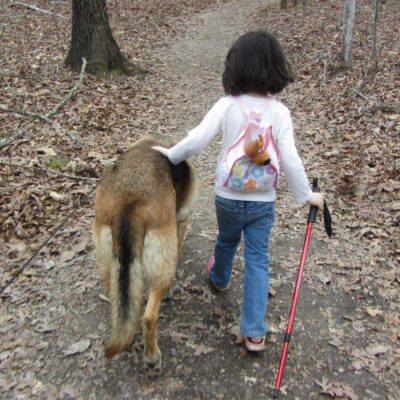 A child enjoying a hiking trail with her dog.