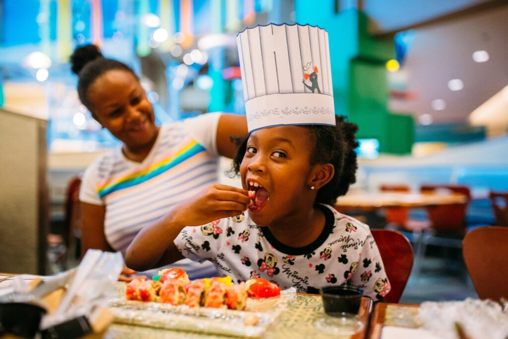 A child enjoying a Ratatouille-themed cooking class.