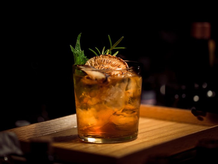 A cocktail beverage on a wooden tray