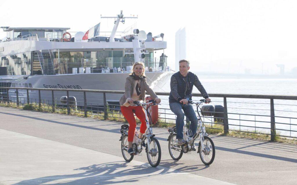 A couple biking past a European river cruise boat