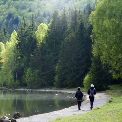 A couple hiking along a mountain lake.