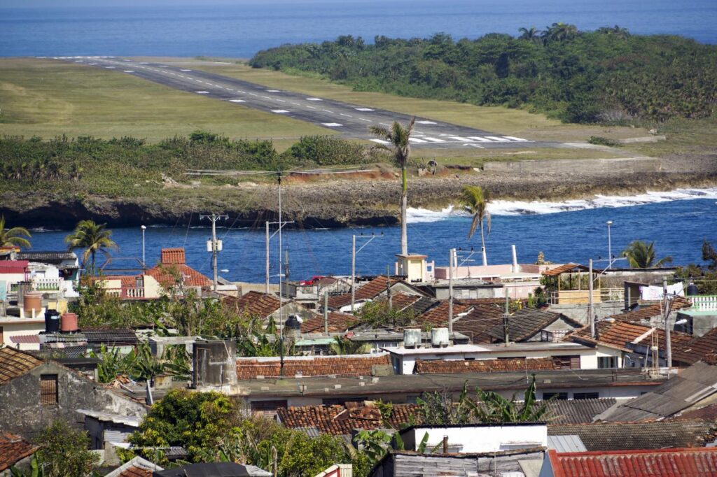 A Cuban airstrip near the ocean and a tile-roofed neighborhood