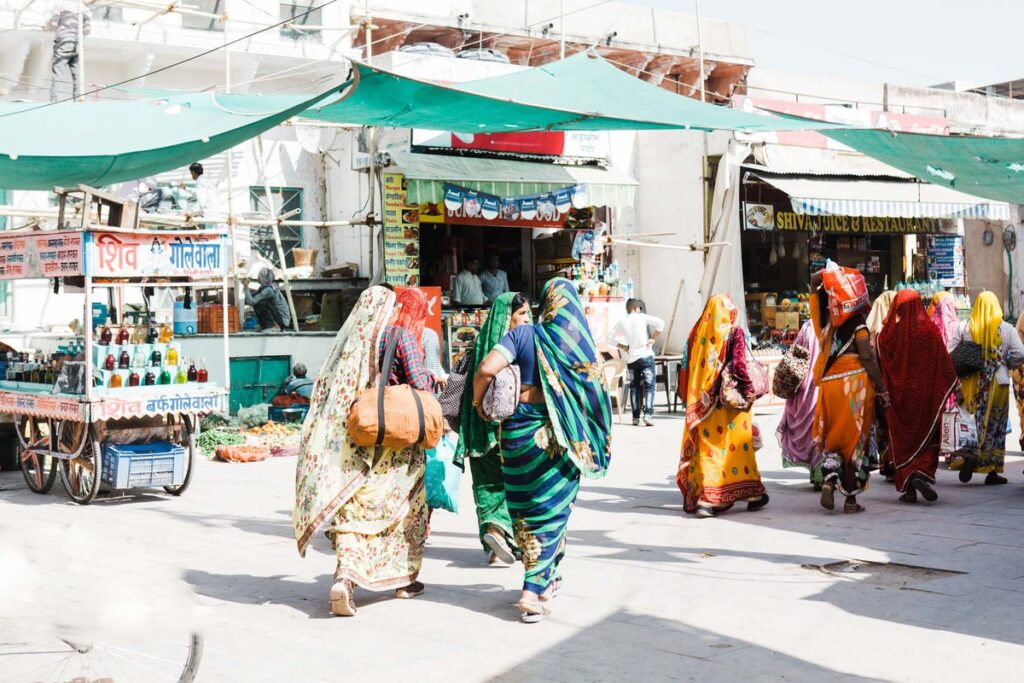 A few groups of women dressed in saris moving through an outdoor market in India