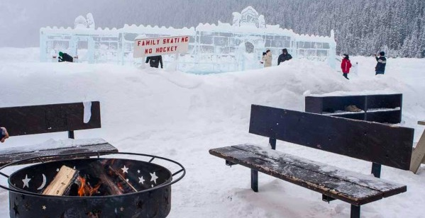 A fire pit and benches on frozen Lake Louise.