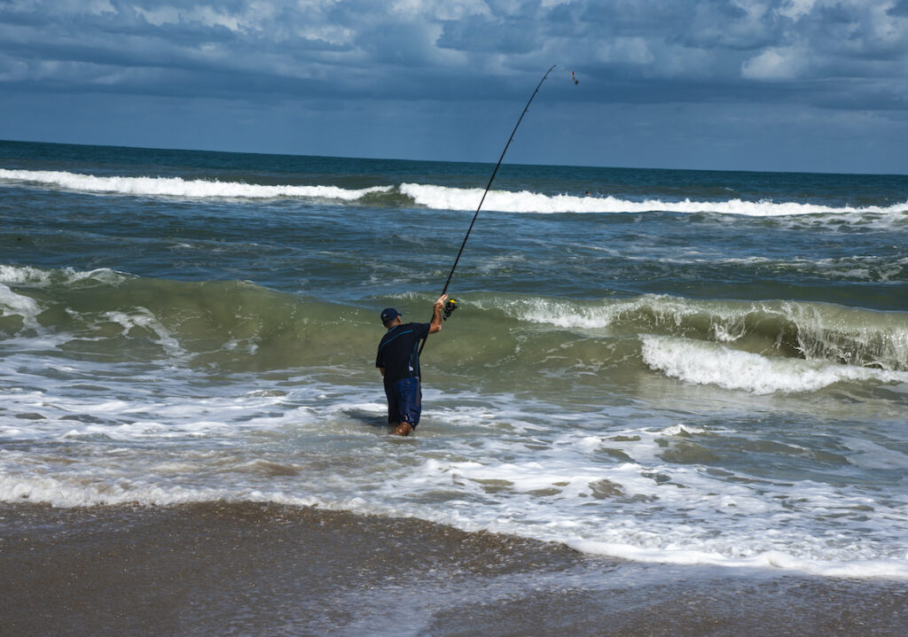 A fisherman casting a line on Cocoa Beach in Florida.