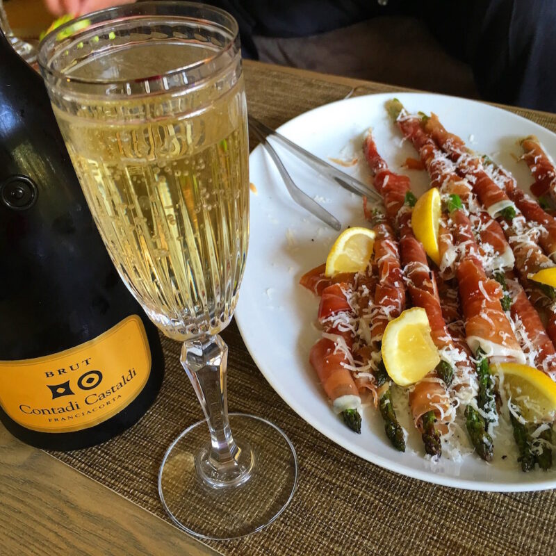 A glass of champagne and proscuitto-covered asparagus.