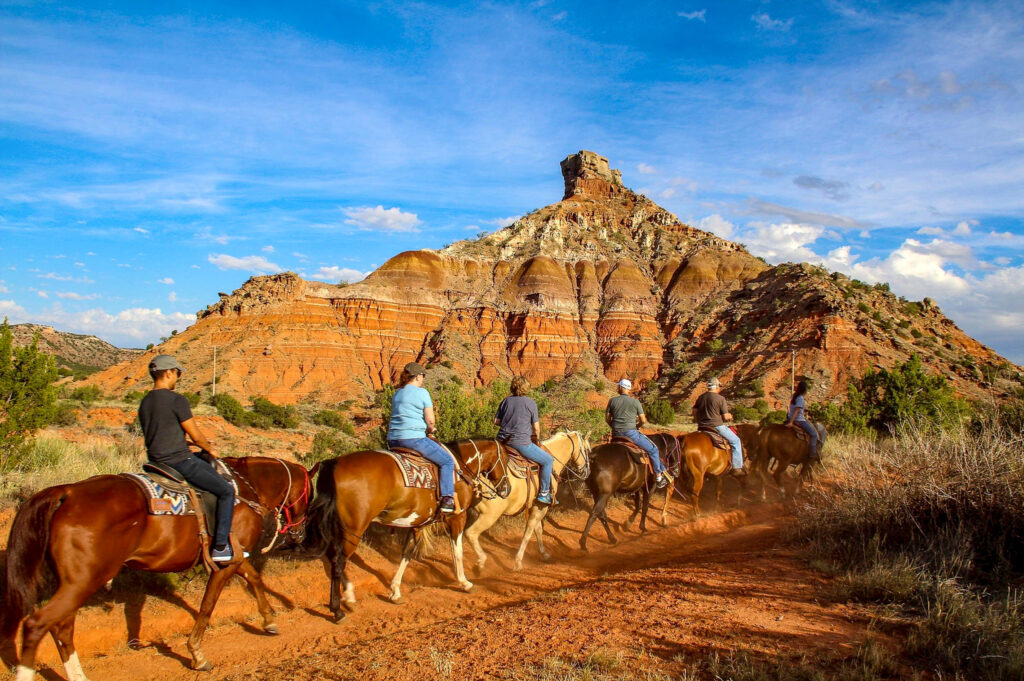 A group takes a horseback ride through Palo Duro Canyon.