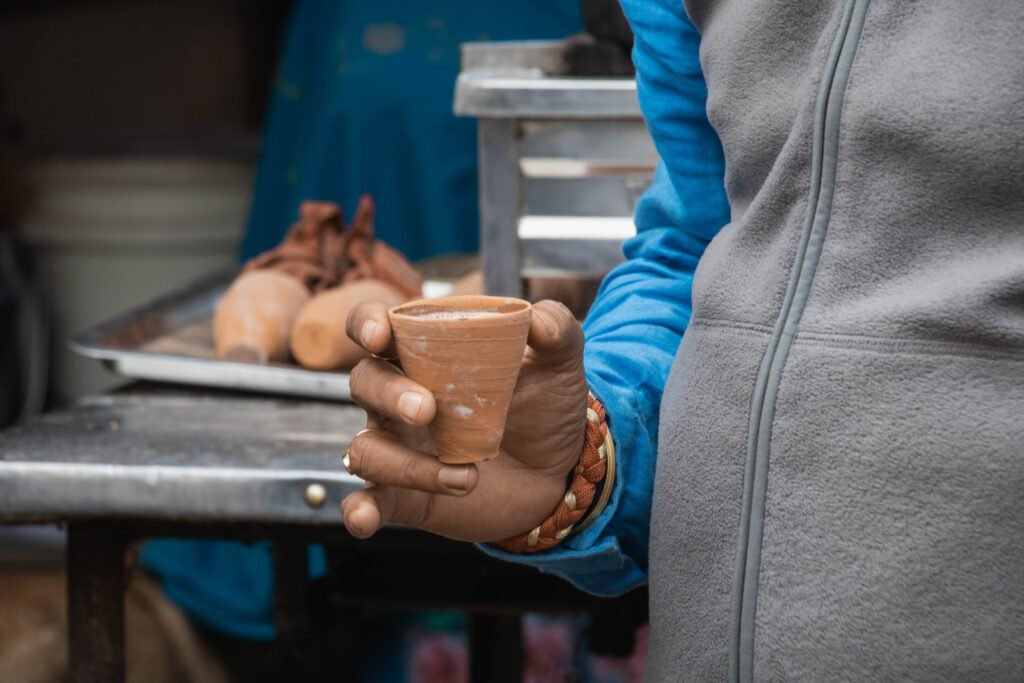 A hand holding a kulhar of chai