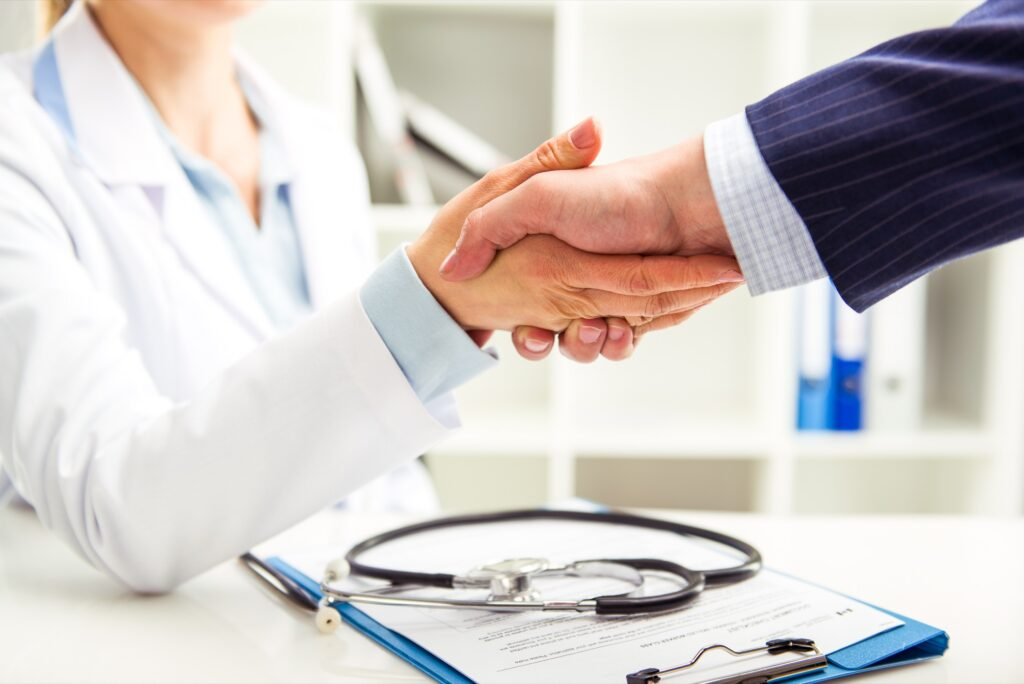 A health insurance provider shakes hands with a patient.