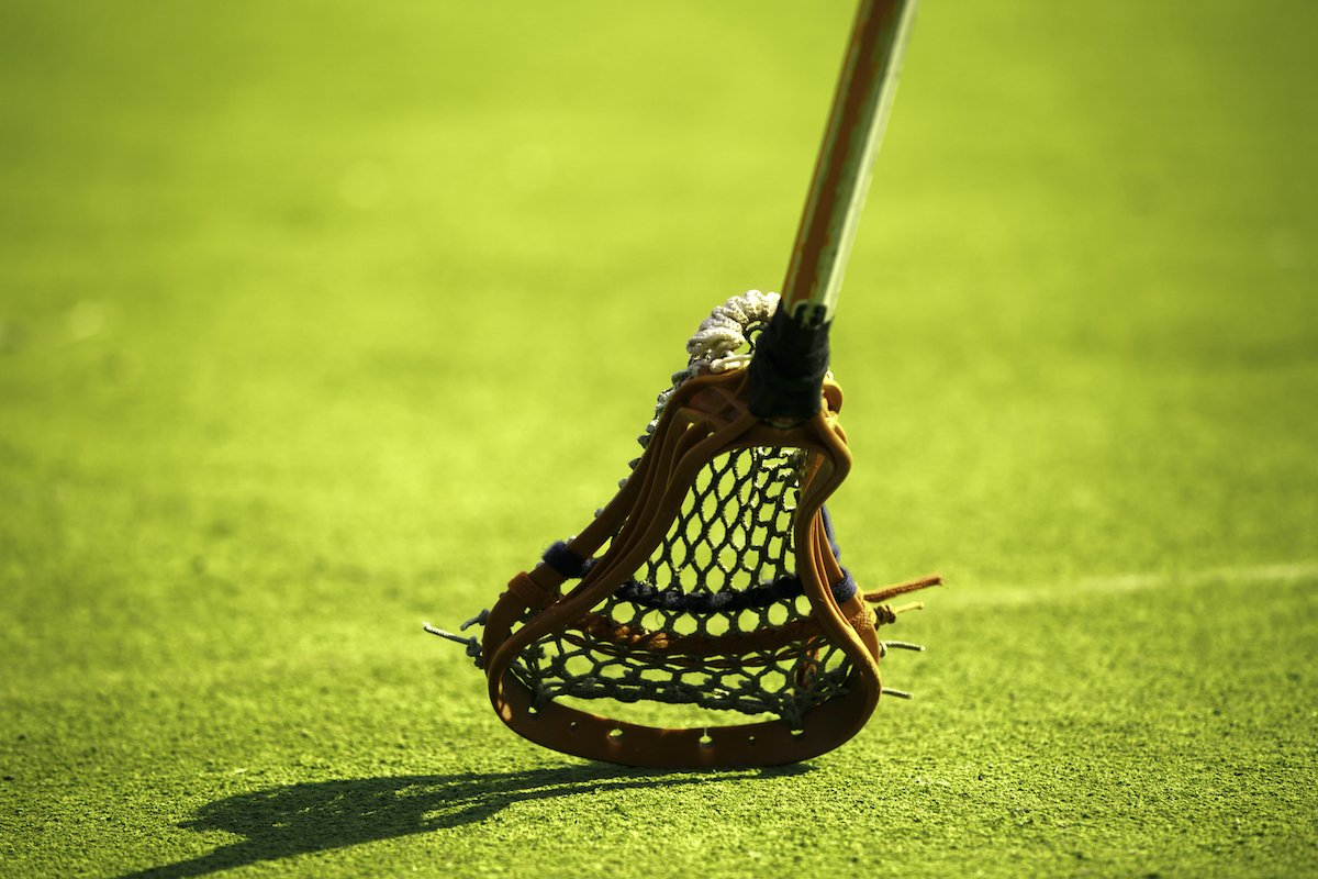 A lacrosse stick hitting the grass.