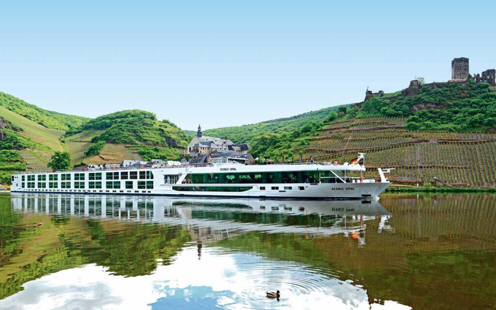 A large riverboat cruising past a European vineyard