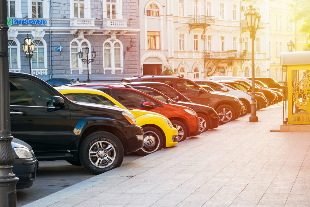 A line of cars parked on a European street.