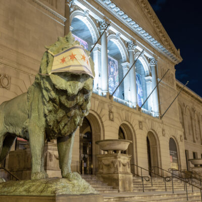 A lion statue wearing a mask outside the Art Institute of Chicago.