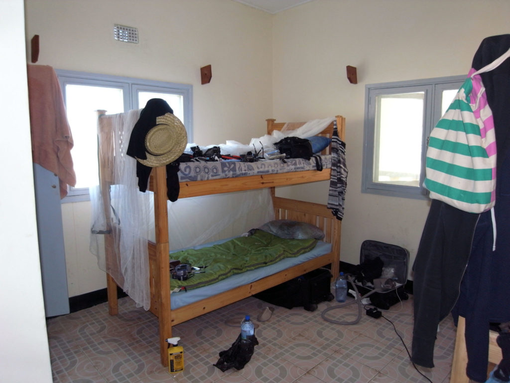 A messy volunteer room with bunk beds
