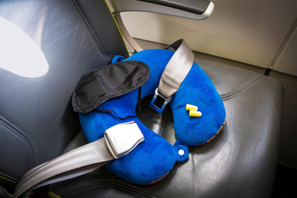 A neck pillow, eye mask, and earwplugs on a plane.