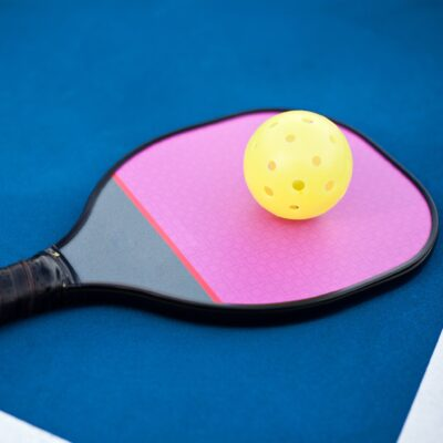 A pickleball paddle and ball on a court.