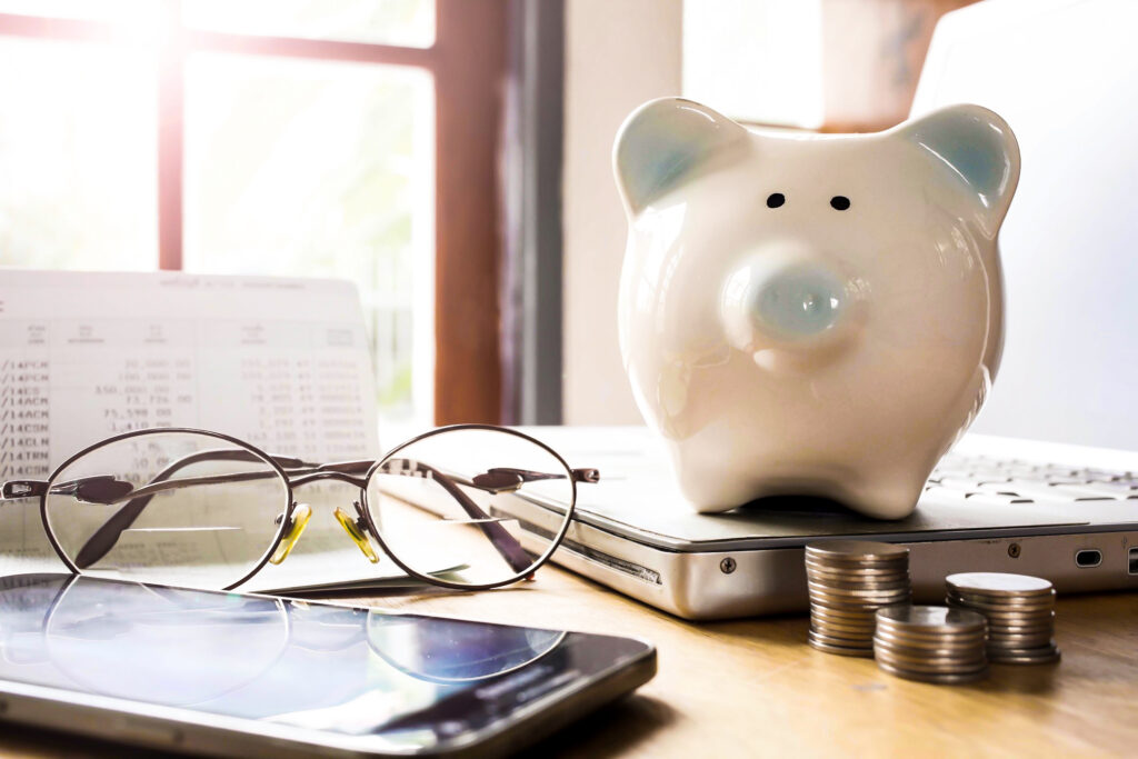 A piggybank watches over its financial records.