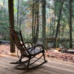 A rocking chair facing the woods.