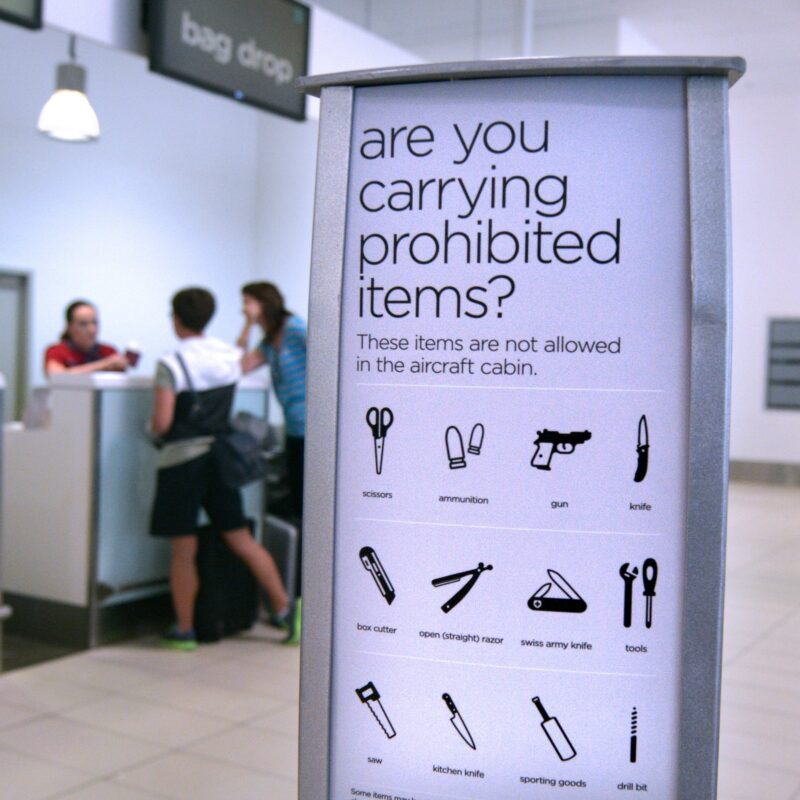 A sign in an airport warning passengers about prohibited items.