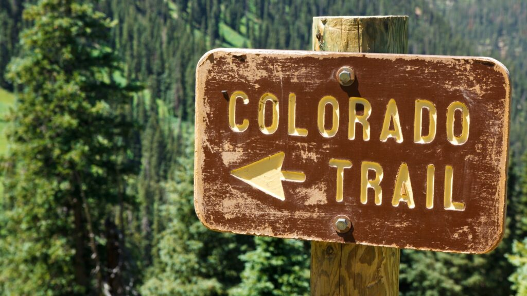 A sign pointing to a trail in the Rocky Mountains.