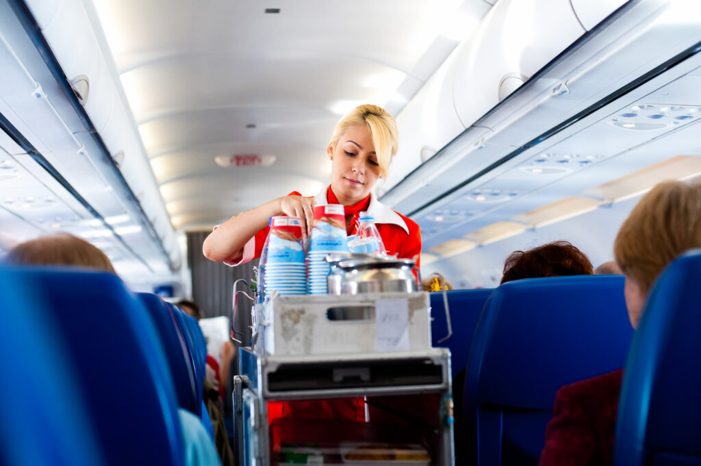A stewardess with a snack and drink cart on an airplane