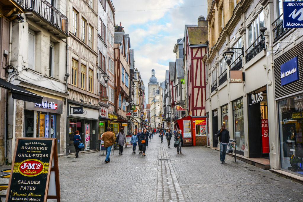 A street full of shops and restaurants in Rouen, France.