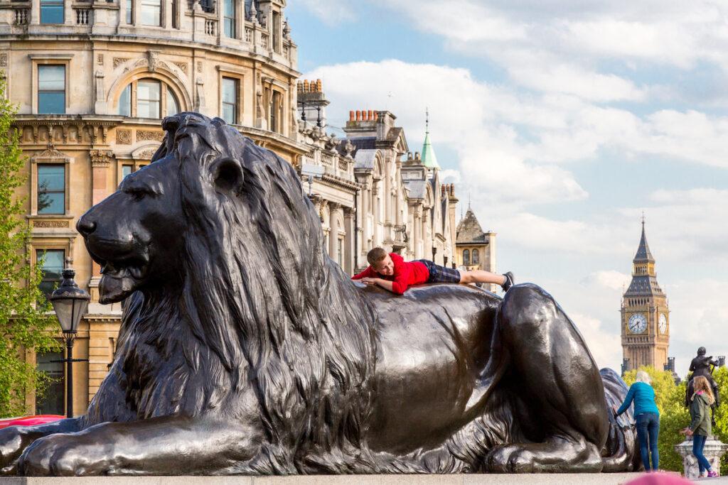 A tourist climbing the lions in Trafalgar Square.