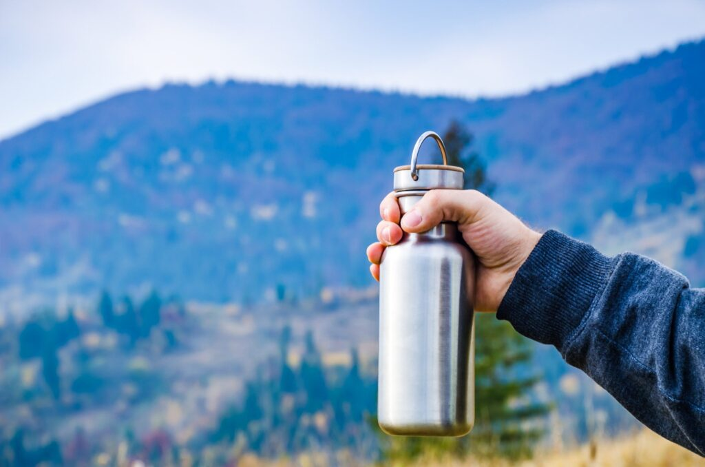 A traveler holds a reusable water bottle.