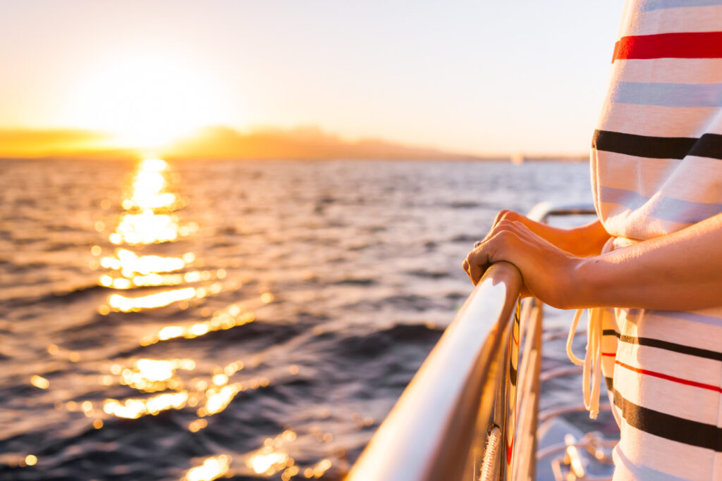 A traveler watches the sunset from a boat.