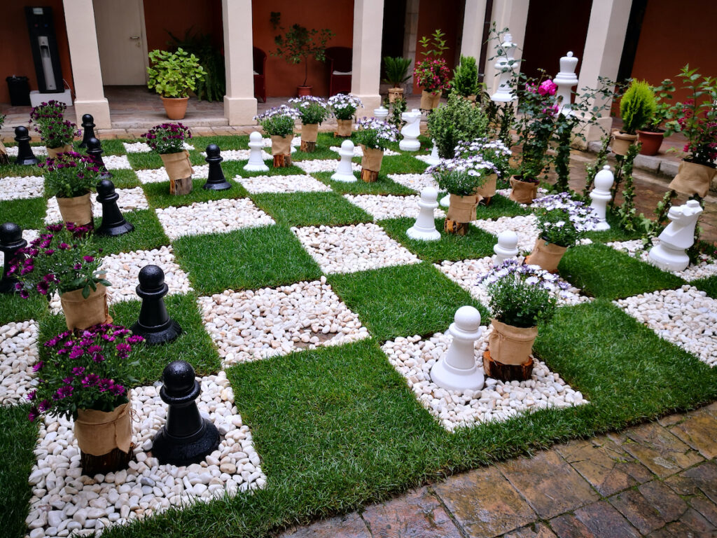 A walkable chess board made of grass and plants.