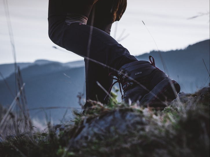 A woman hiking with pants tucked into her socks to protect from ticks