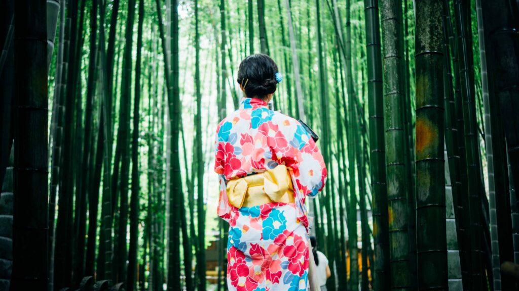 A woman in kimono walking through a bamboo grove