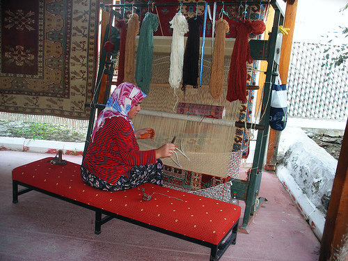 A woman sits at a loom weaving a Turkish rug similar to those sold in the Grand Bazaar in Istanbul