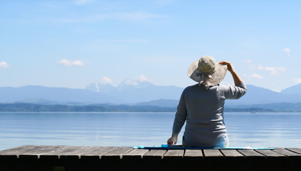 A woman sits on the edge of a dock.