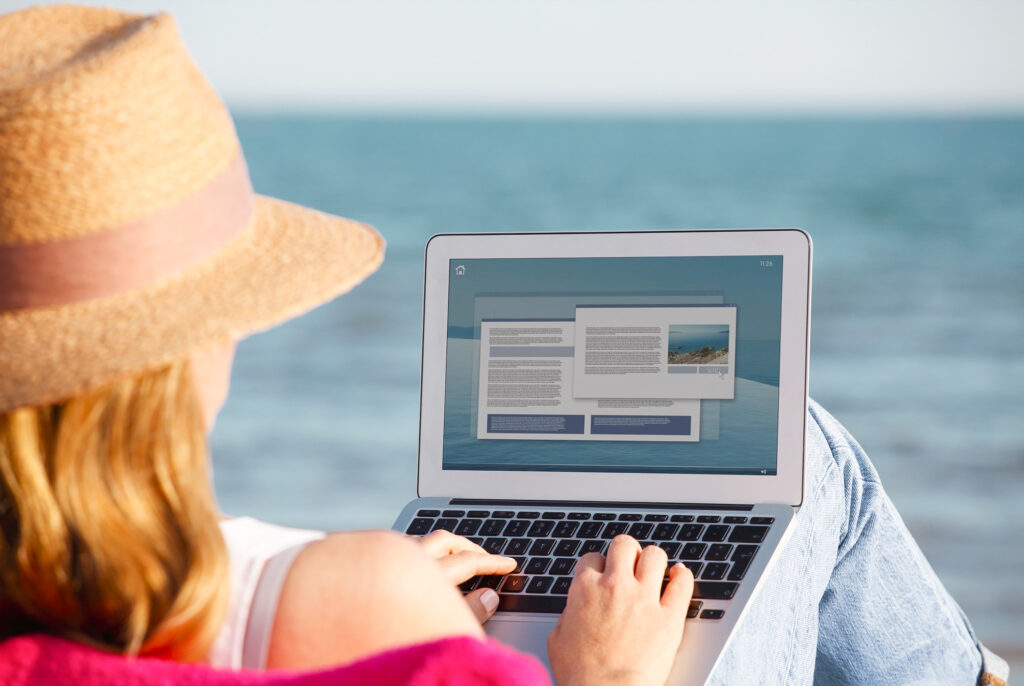 A woman using her laptop on a beach.