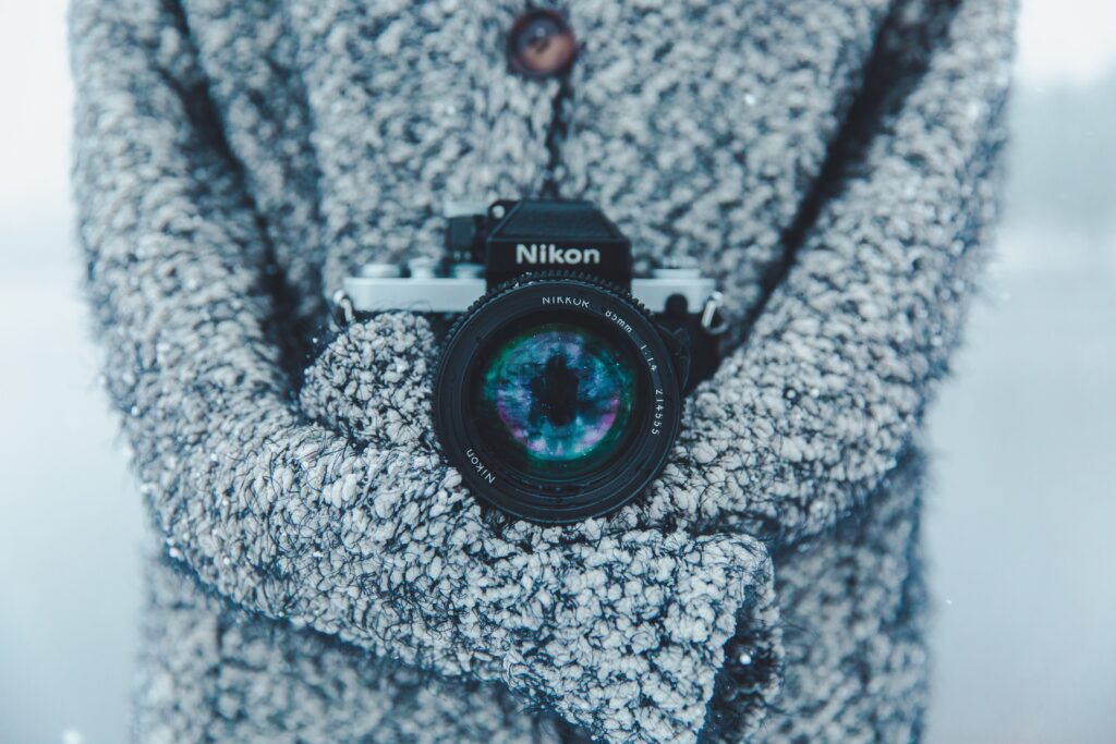 a woman wearing a very cozy long-sleeved sweater holding a large nikon camera