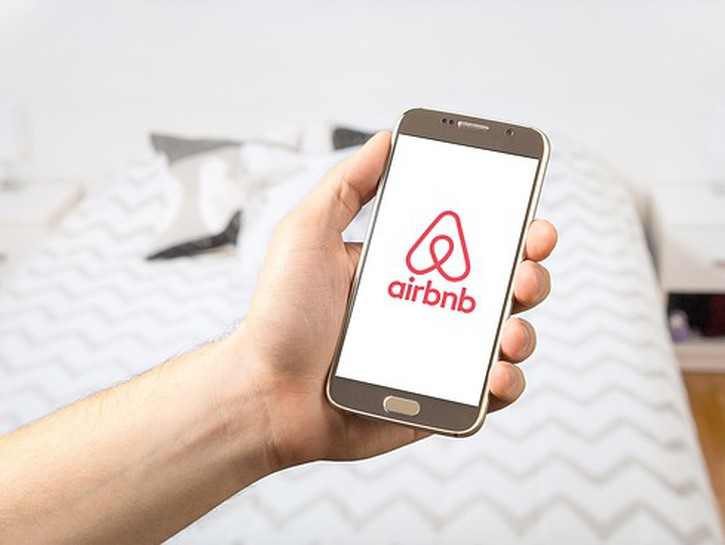 Airbnb logo on phone being held up by man's arm