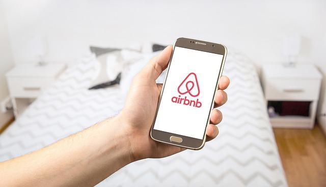 Airbnb logo on phone held in hand in bedroom