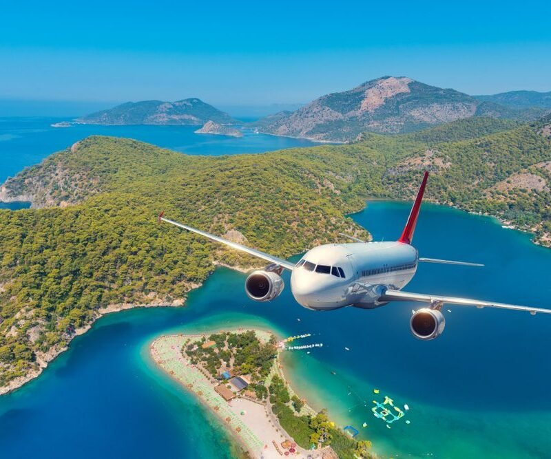 airplane flying out of island over ocean