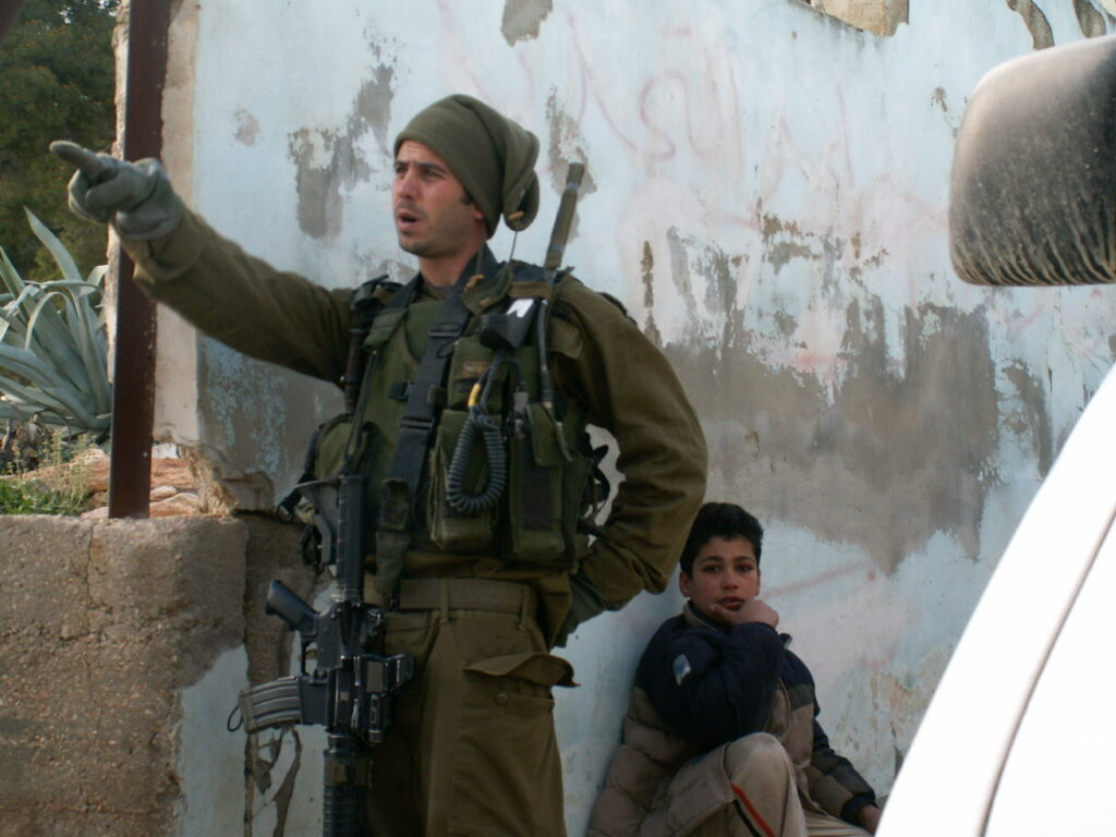 An Israeli soldier giving orders in a Palestinian village.