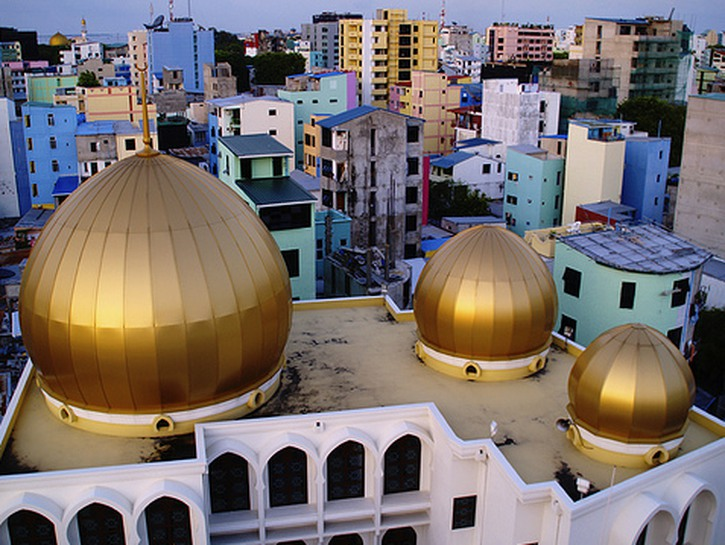 An overhead image of a mosque in Malé, the capital of the Maldives, with its three gold domes, or qu