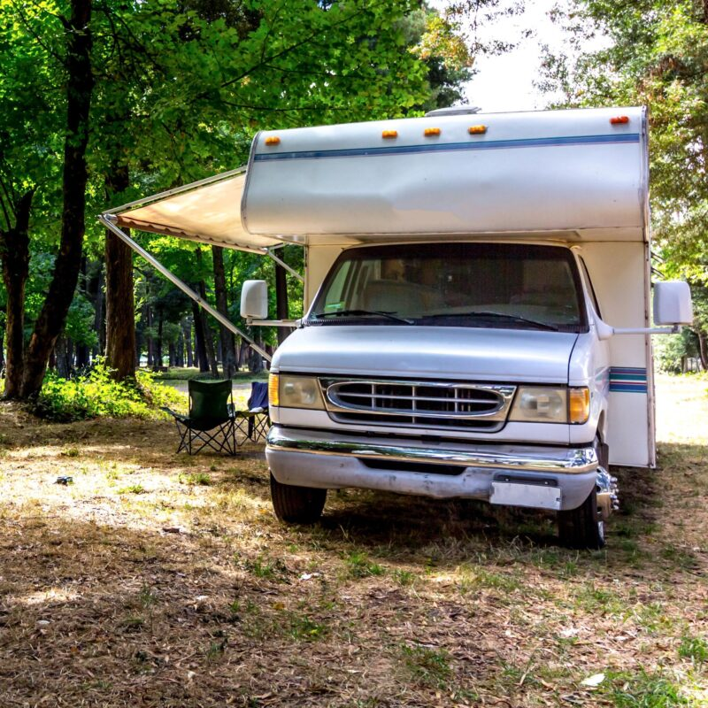 An RV parked at a camping site in a forest.