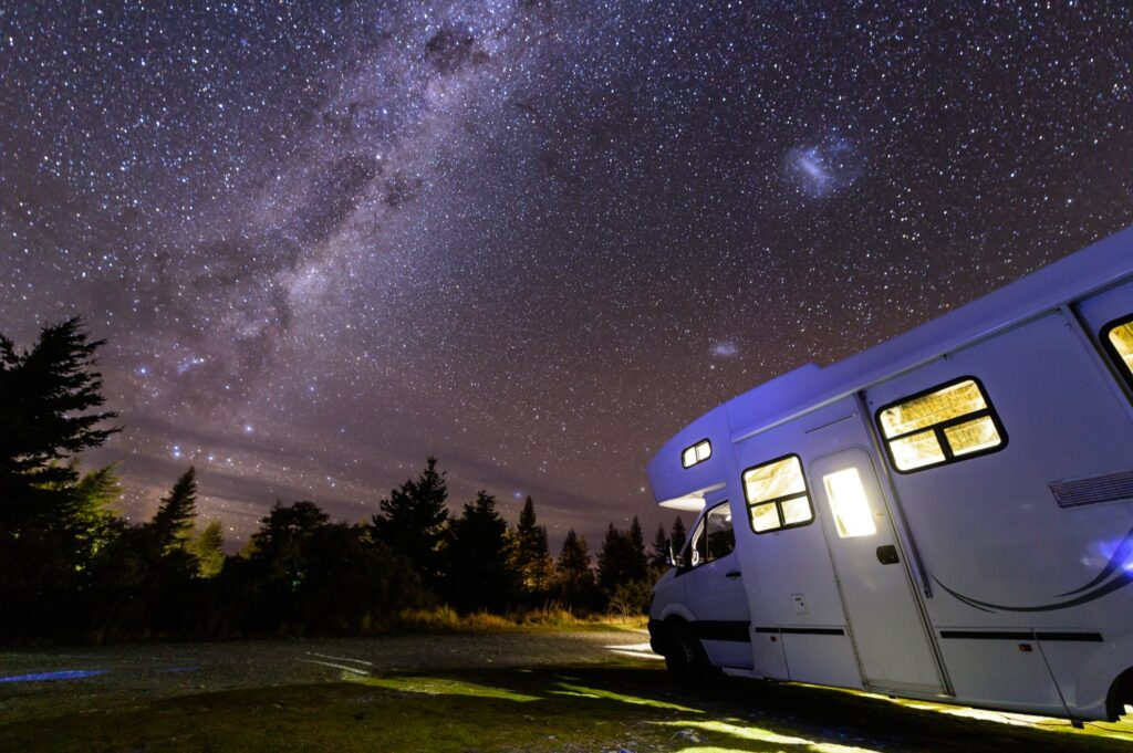 An RV parked under the night sky.
