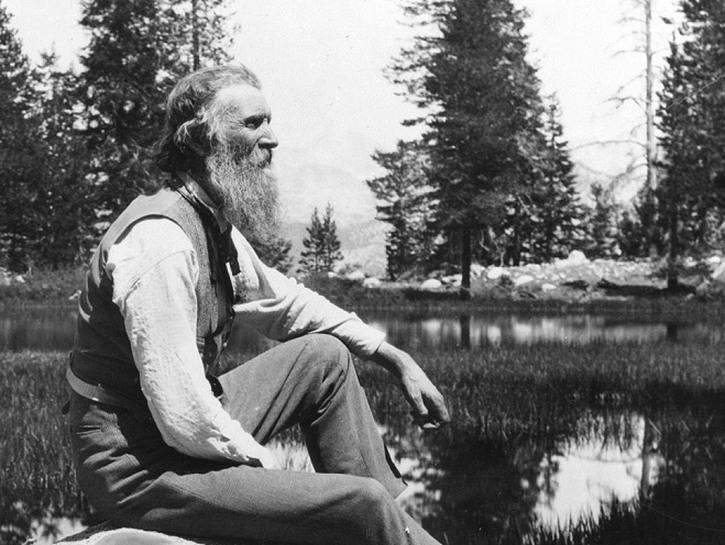 Author John Muir sitting by a stream.