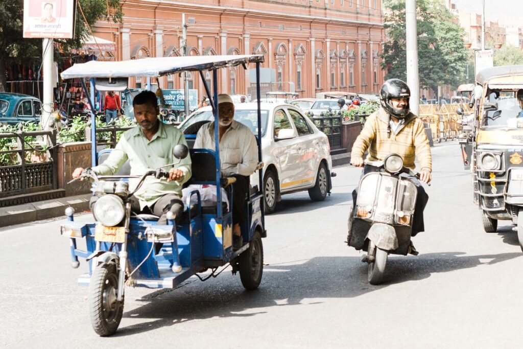 Autorickshaws, a car, and a motorcycle on a busy Indian street