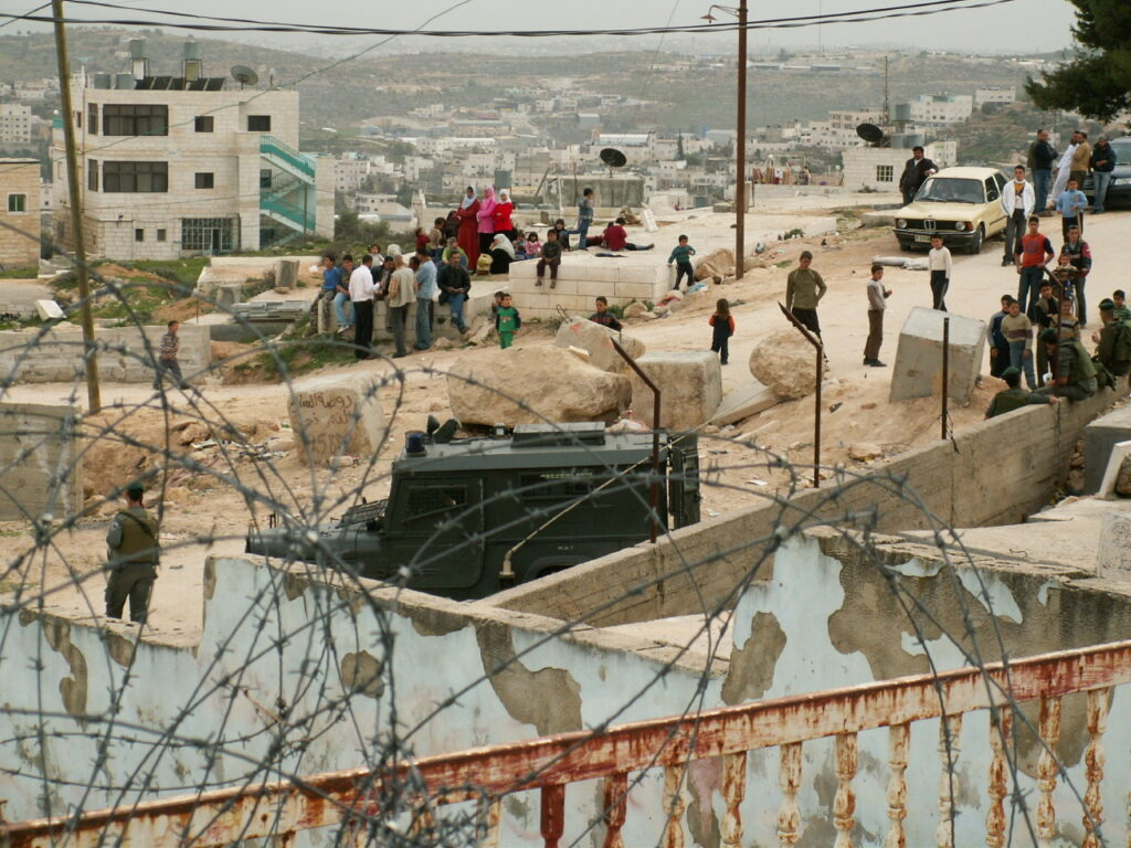 Barbed wire and Israeli soldiers in a Palestinian village.